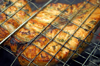 Close-up salmon steak cooking on a grill