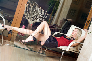 Sexy blond woman relaxing in the armchair