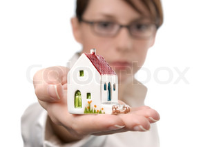 Image of business woman holding toy house on her palm