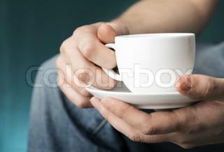 Hænder, der holder en hvid kaffekop