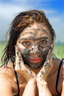 Pretty young woman having mud bath outdoors
