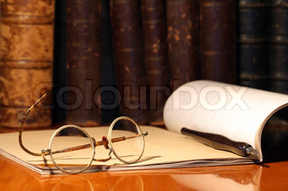Vintage still life with old spectacles, paper notebook and pen on background with books