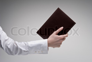 Woman's hand holding brown diary with leather hardcover over light background