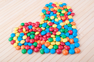 many colored candy on a wooden table