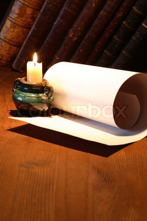 Old paper near lighting candle and stack of vintage books on wooden surface