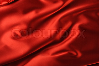 red satin background. A satiny fabric with beautiful light-shadow waves