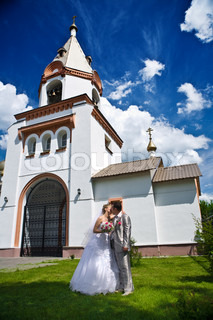 Newly married kiss on a background of church