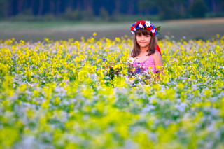 Adorable girl with bouquets of flowers in a blossom field