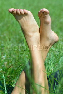 person resting her feet in the fresh spring vegetation under sunshine
