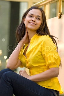 beautiful young woman in yellow blouse sits on the street
