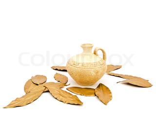 Photo of ancient beige vase and golden bay leaves against white background