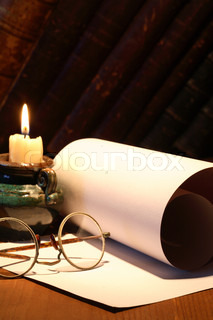 Scroll and old spectacles near lighting candle on dark background with vintage books