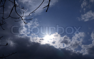 Blue sky with sun and dark and white clouds with tree