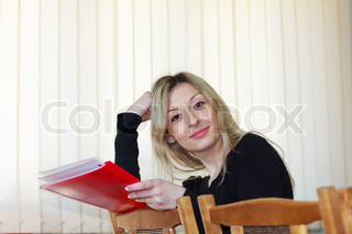 beautiful young girl with long blond hair and dark eyes sits leaning back in his chair with a red folder in his hands