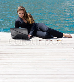 woman in black business suit lying with laptop near the sea