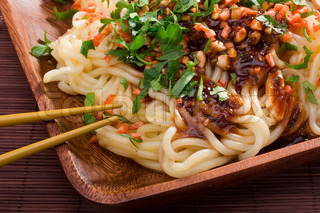 Prepared Asian noodles on a brown wooden plate.
