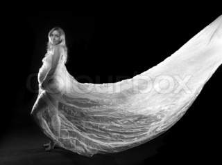 beautiful young pregnant woman wrapped in a white veil on a black background with a long train