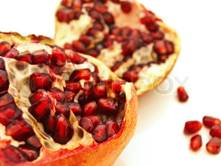 broken ripe pomegranate over the white background