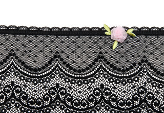Black lace with rose satin flower on white background