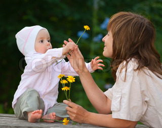 A charming one-year child gives a flower to his mother