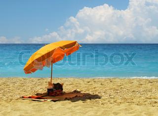Gul paraply på varme sandstrand ved turkis blå ocean