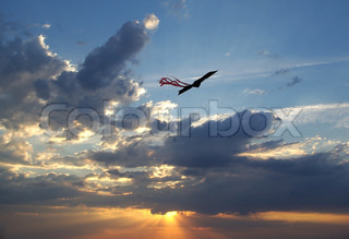 Kite flying in the sky against clouds on sunset