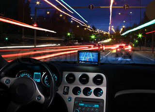 Night view of navigating with gps satellite navigator in traffic seen from car cabin