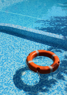 Life saver buoy ring floating in turquoise swimming pool