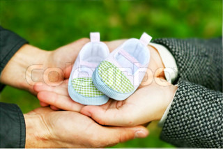 Pregnant couple holding a little boot in their arms. Close-up.
