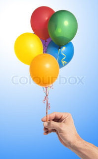 Hand holding colorful air balloons over blue background