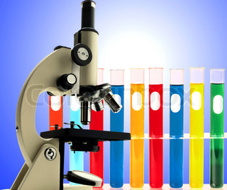 Laboratory metal microscope and test tubes with liquid over blue