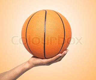 Basketball in hand over orange background
