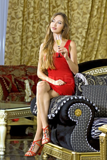 beautiful happy woman in red dress on a sofa with glass of champagne