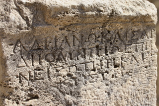 Ancient Greek writing carved on old limestone surface