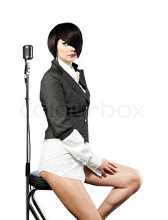 Young woman with fashion haircut sitting back to the vintage microphone, on white