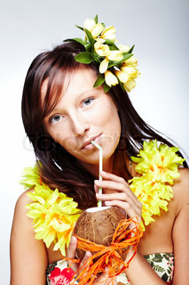 Beautiful exotic girl with Hawaiian accessories drinking coconut juice