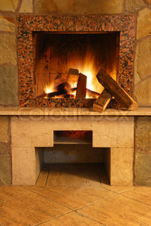 Fireplace. Flaring fire in a fireplace the reveted wild stone and a marble
