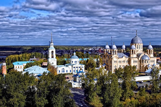 Snowy the Transfiguration Cathedral, beige Kresovozdvizhensky Cathedral with gray zinc domes, buildings, towers and walls of St. Nicholas Monastery against the blue sky, gray clouds and a yellow-green trees (Verhoturie city of Sverdlovsk Region)