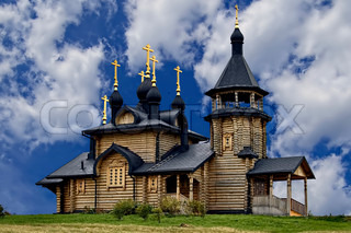 Wooden Church of All Saints in the land of Siberia with a black roof and a gold cross on a background of blue sky and white clouds (Verkhotursky district, Sverdlovsk region)