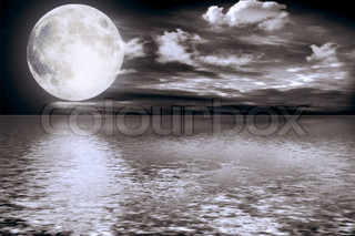 The full moon in clouds reflected in water