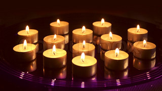Small Christmas candles burning on glass tray, on dark background