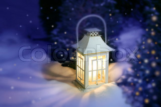 White Christmas lantern in snow, with yellow candle light, on mysterious violet background