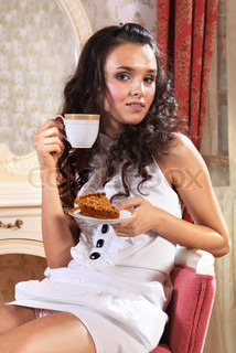 girl with piece of cake and cup of tea with comehither eyes