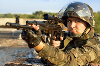 Portrait of young soldier in camouflage with machine gun
