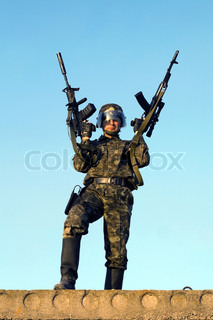 Soldier in camouflage staying with two rifles