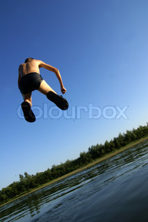 Boy jumps in small river