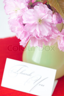 sakura flower in a vase and a card signed thank you on a red background