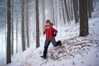Blurred motion of running man in winter mountain forest