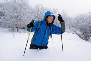 A backpacker man going through deep snow in the winter forest
