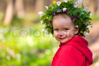 A little girl with a wreath in spring forest